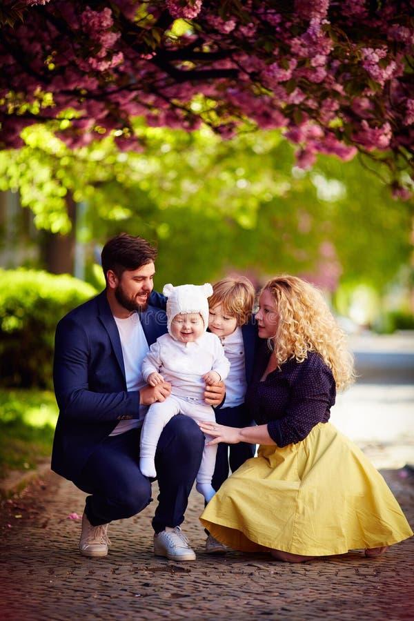 Portret van gelukkige familie op de gang langs de bloeiende de lentestraat royalty-vrije stock afbeeldingen