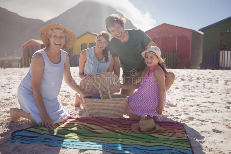 Portret van gelukkige familie van meerdere generaties door picknickdeken bij strand stock fotografie
