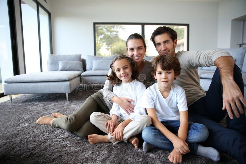Portret van gelukkige familiezitting op de vloer royalty-vrije stock afbeeldingen