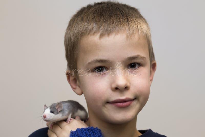 Portret van gelukkige glimlachende grappige leuke knappe kindjongen met de witte hamster van de huisdierenmuis op schouder op lic royalty-vrije stock afbeeldingen