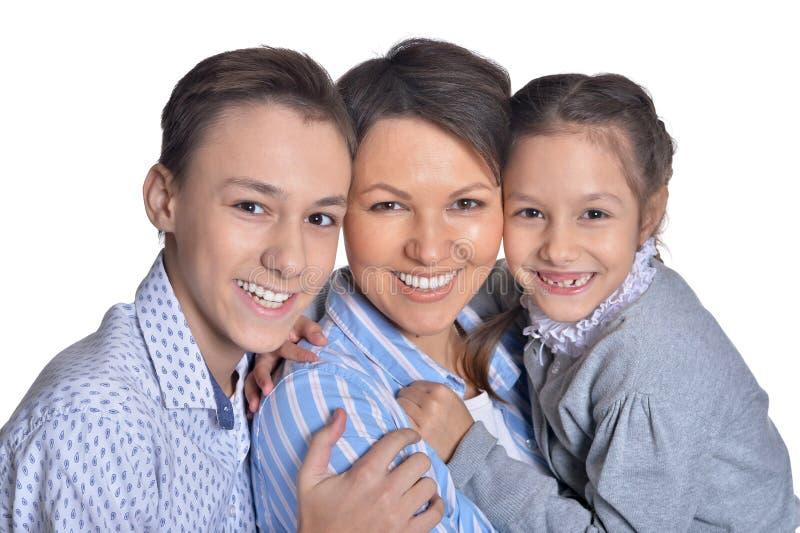 Portret van gelukkige glimlachende moeder en kinderen die samen stellen royalty-vrije stock afbeelding
