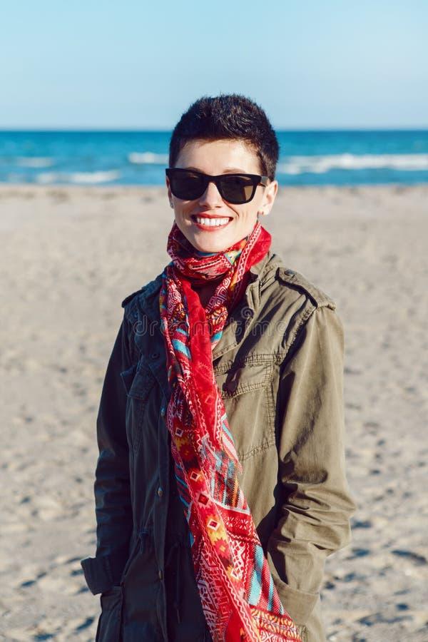 Portret van gelukkige glimlachende mooie Kaukasische witte donkerbruine vrouw met kort haar in groen jasje, rode sjaal en zonnebr royalty-vrije stock fotografie