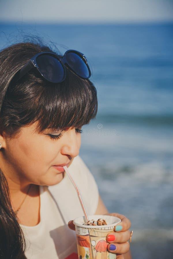 Portret van gelukkige glimlachende mooie te zware jonge vrouw die in witte T-shirt zoete koffie drinken door stro in openlucht bi stock foto