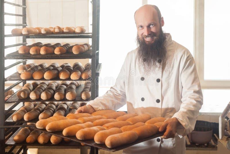 Portret van gelukkige glimlachende trotse jonge volwassen bakker met lange baard in witte eenvormige status in zijn werkplaats en stock foto's