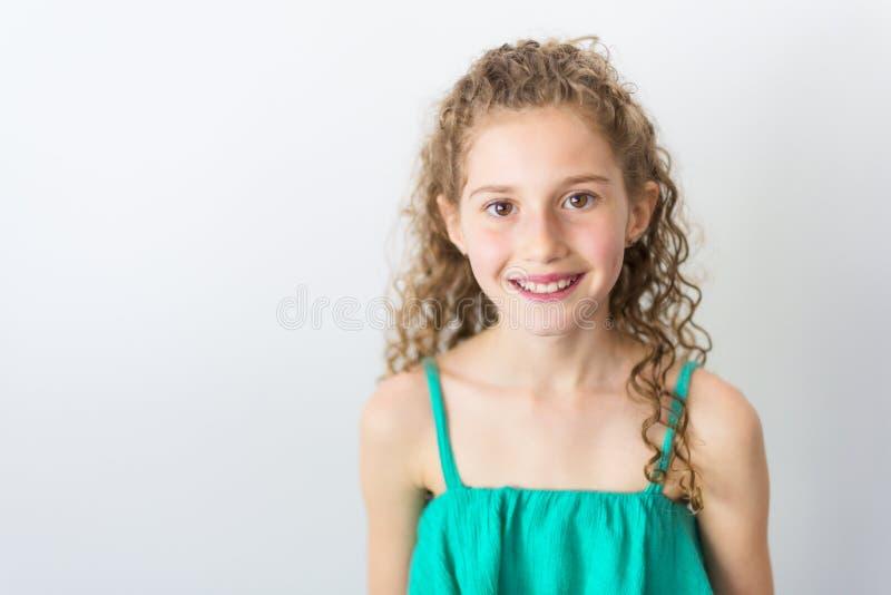 Portret van gelukkige, glimlachende, zekere 9 jaar oud meisjes met krullend die haar, op grijs wordt geïsoleerd royalty-vrije stock foto