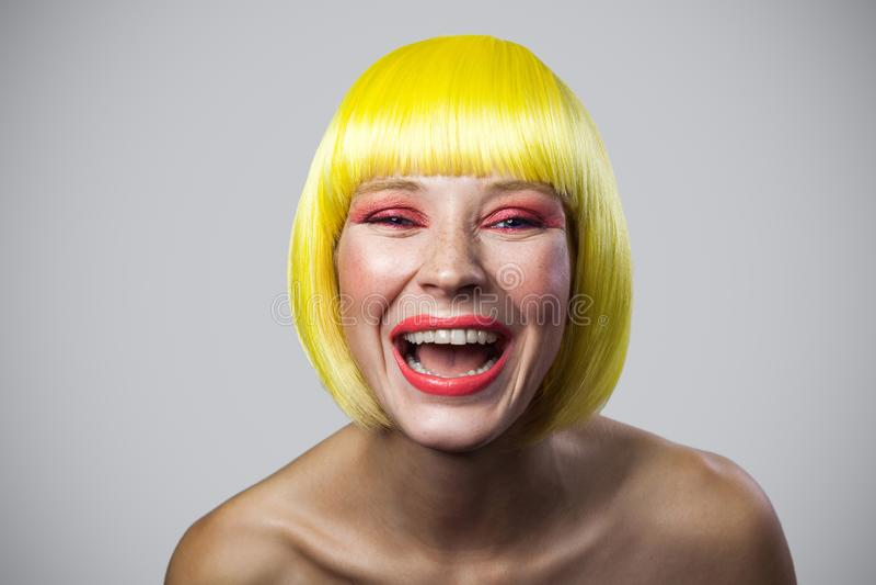 Portret van gelukkige grappige leuke jonge vrouw met sproeten, rode make-up en gele pruik die camera bekijken en met opgewekt gez stock foto's
