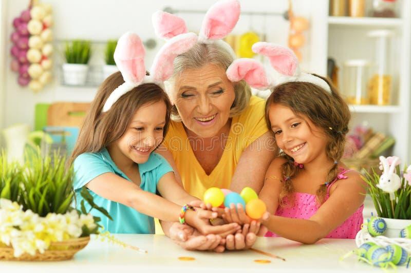 Portret van gelukkige grootmoeder en kleindochters die paaseieren kleuren royalty-vrije stock afbeeldingen