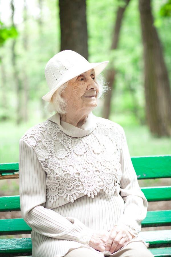 Portret van gelukkige grootmoeder op een parkbank, royalty-vrije stock fotografie