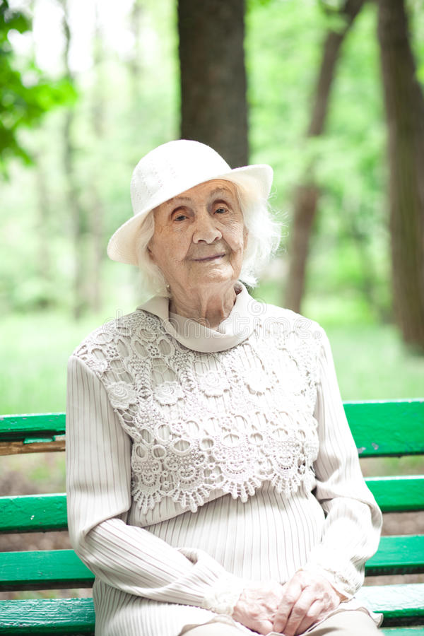 Portret van gelukkige grootmoeder op een parkbank, royalty-vrije stock foto