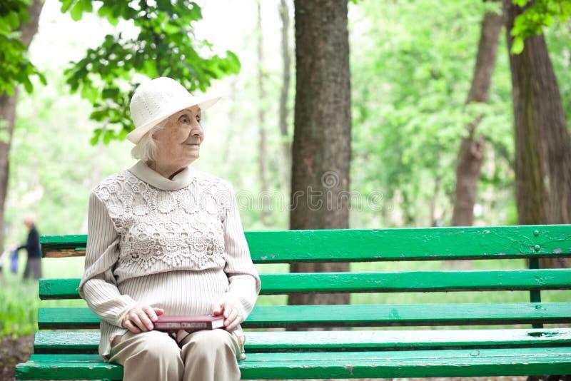 Portret van gelukkige grootmoeder op een parkbank, stock foto's
