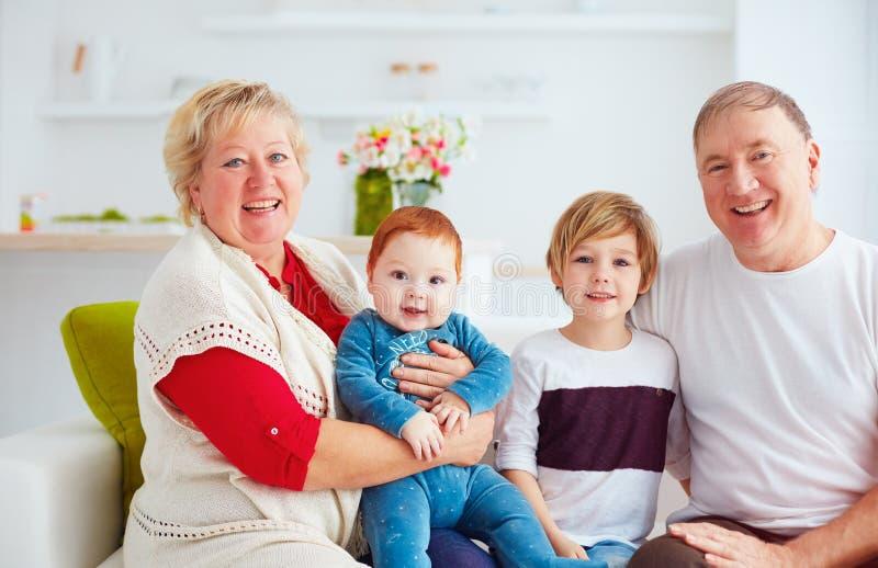 Portret van gelukkige grootouders en kleinkinderen thuis royalty-vrije stock afbeelding