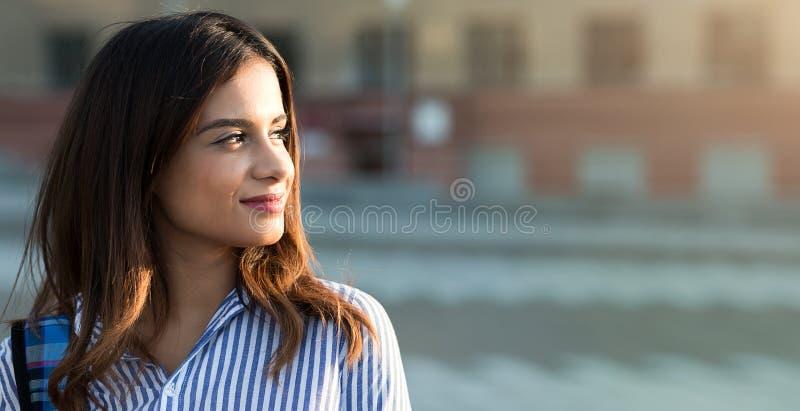 Portret van gelukkige het glimlachen vrouw status op het vierkant met van het sunligthgloed en exemplaar ruimte royalty-vrije stock fotografie