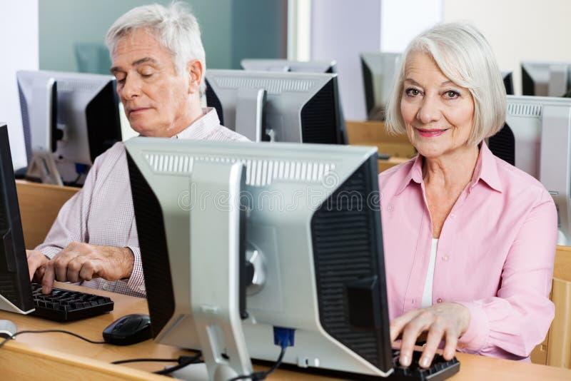 Portret van Gelukkige Hogere Vrouw die Computer in Klaslokaal met behulp van stock fotografie