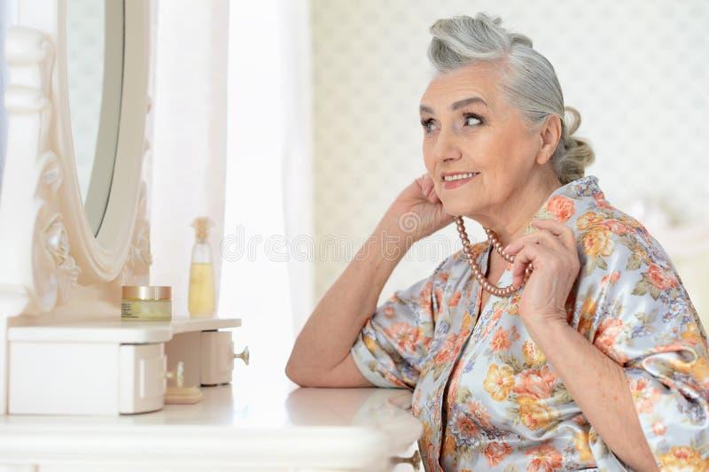Portret van gelukkige hogere vrouw die make-up toepassen royalty-vrije stock afbeelding