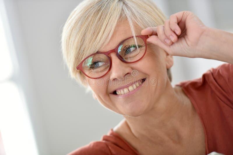 Portret van gelukkige hogere vrouw die rode oogglazen dragen royalty-vrije stock foto