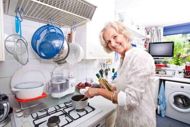 Portret van gelukkige hogere vrouw die voedsel in binnenlandse keuken voorbereiden royalty-vrije stock afbeelding