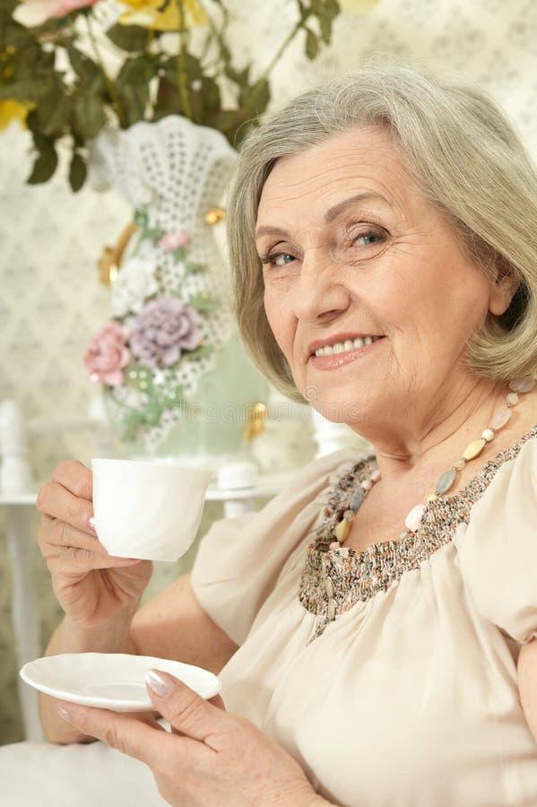 Portret van gelukkige hogere vrouw het drinken thee terwijl thuis het rusten royalty-vrije stock afbeeldingen