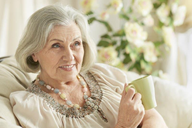 Portret van gelukkige hogere vrouw het drinken thee terwijl thuis het rusten stock foto
