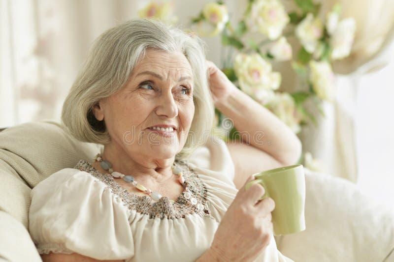 Portret van gelukkige hogere vrouw het drinken thee terwijl thuis het rusten stock afbeeldingen