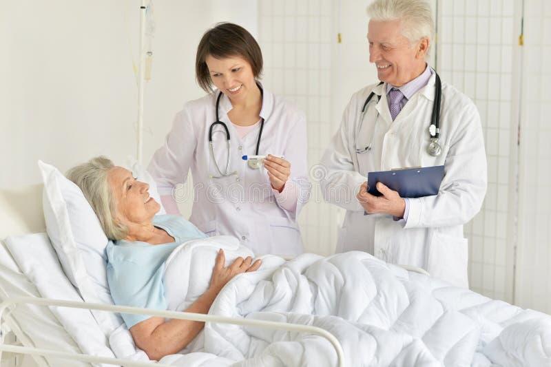 Portret van gelukkige hogere vrouw in het ziekenhuis met gevende artsen stock afbeeldingen
