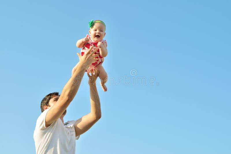 Portret van gelukkige houdende van vader en haar baby in openlucht Papa en kind tegen de zomer blauwe hemel royalty-vrije stock afbeeldingen