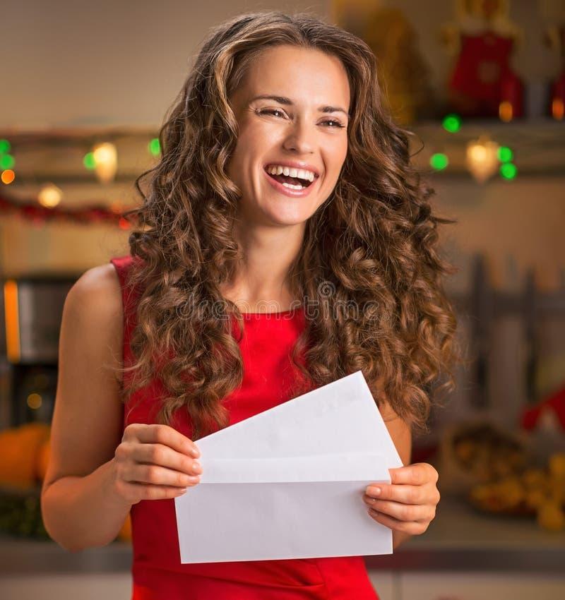 Portret van gelukkige huisvrouw met Kerstmisbrief in keuken royalty-vrije stock foto's