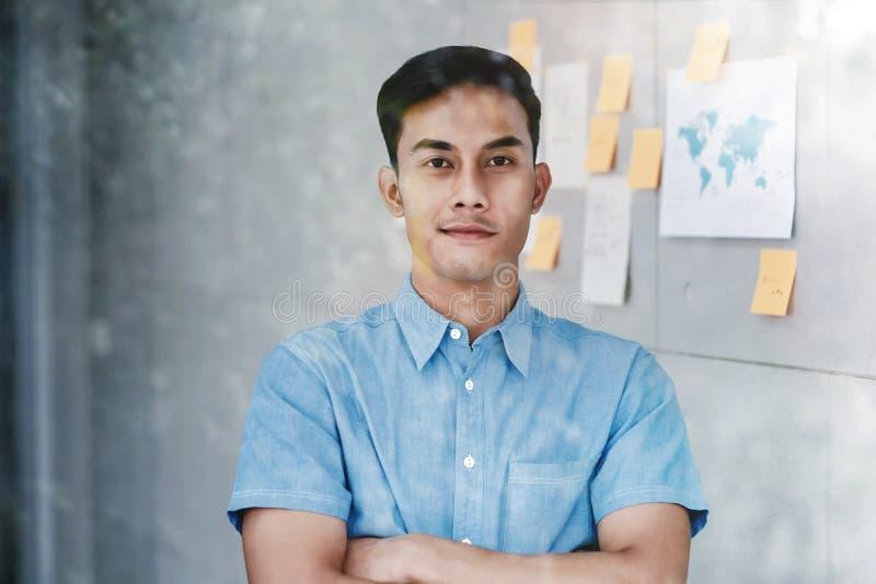 Portret van Gelukkige Jonge Aziatische Zakenman status door de Venster Gekruiste Wapens en het Glimlachen in Bureau royalty-vrije stock foto's