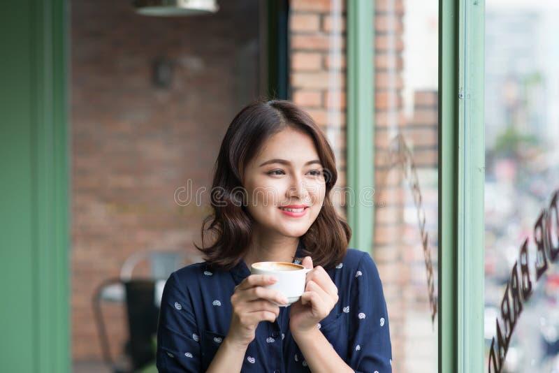 Portret van gelukkige jonge bedrijfsvrouw met mok in handen drinkin stock foto