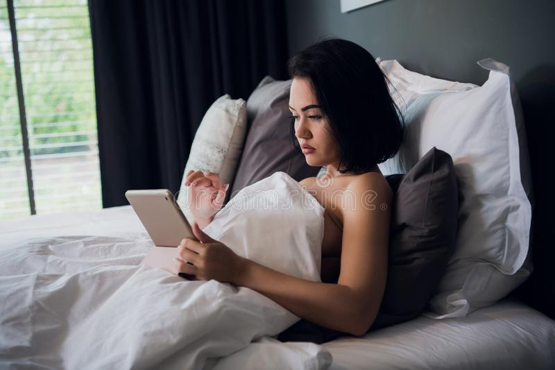 Portret van gelukkige jonge Kaukasische vrouwenzitting in bed, het gebruiken van digitale tablet en het glimlachen stock foto's
