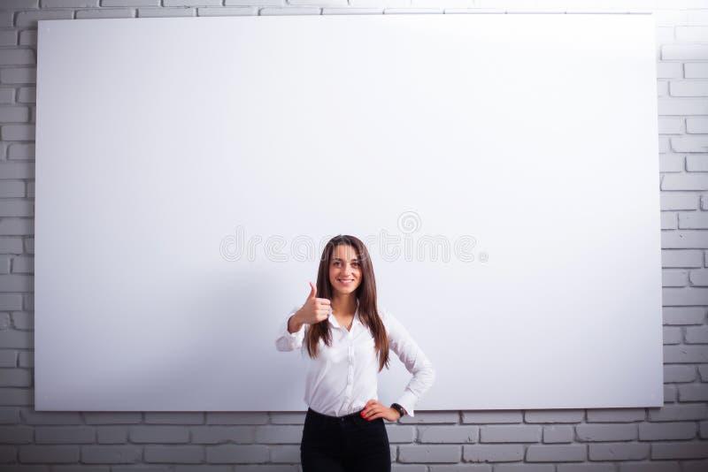 Portret van Gelukkige Jonge Onderneemstervrouw dichtbij op witte muur royalty-vrije stock foto's