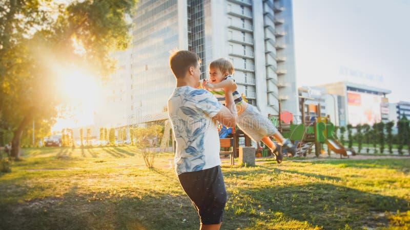 Portret van gelukkige jonge vader die en zijn het glimlachen koesteren spinnen weinig peuterzoon in park royalty-vrije stock fotografie