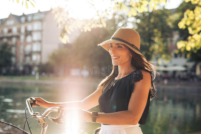 Portret van gelukkige jonge vrouw bij het stadspark die met haar fiets lopen royalty-vrije stock foto's