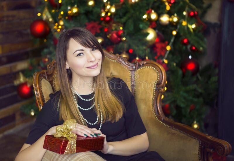 Portret van gelukkige jonge vrouw dichtbij de Kerstboom royalty-vrije stock afbeeldingen