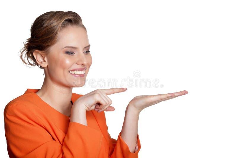 Portret van gelukkige jonge vrouw die aan het recht op witte achtergrond richten royalty-vrije stock foto