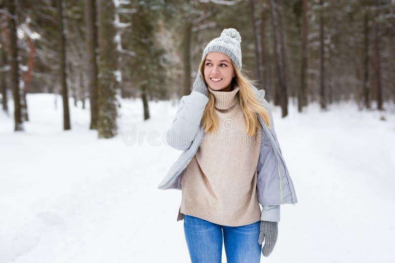 Portret van gelukkige jonge vrouw die in het winterbos loopt stock afbeeldingen