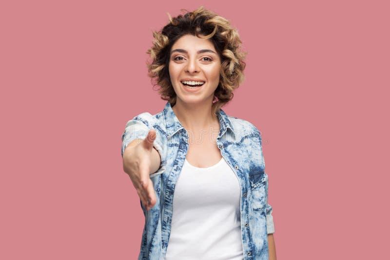 Portret van gelukkige jonge vrouw met krullend kapsel in toevallig blauw overhemds zich bevindt, toothy glimlach, kijkend en geve stock afbeelding
