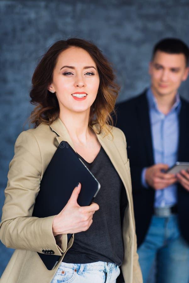 Portret van gelukkige jonge vrouwenholding laptop en het bekijken camera royalty-vrije stock afbeelding