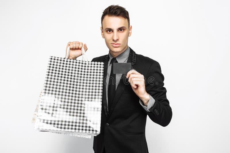 Portret van gelukkige jonge zakenman in zwart kostuum, met pakketten royalty-vrije stock afbeeldingen