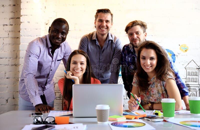 Portret van gelukkige jongeren in een vergadering die camera en het glimlachen bekijken Jonge ontwerpers die aan creatief samenwe royalty-vrije stock foto's