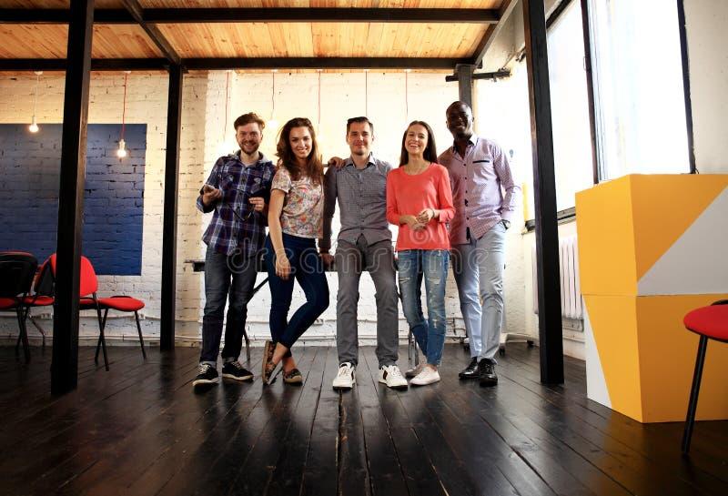 Portret van gelukkige jongeren in een vergadering die camera en het glimlachen bekijken Jonge ontwerpers die aan creatief samenwe stock afbeeldingen