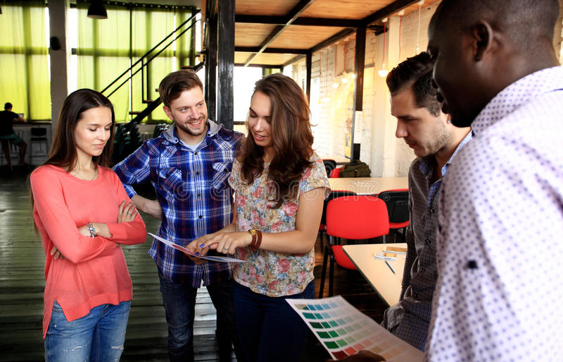 Portret van gelukkige jongeren in een vergadering die camera en het glimlachen bekijken Jonge ontwerpers die aan a samenwerken stock afbeeldingen