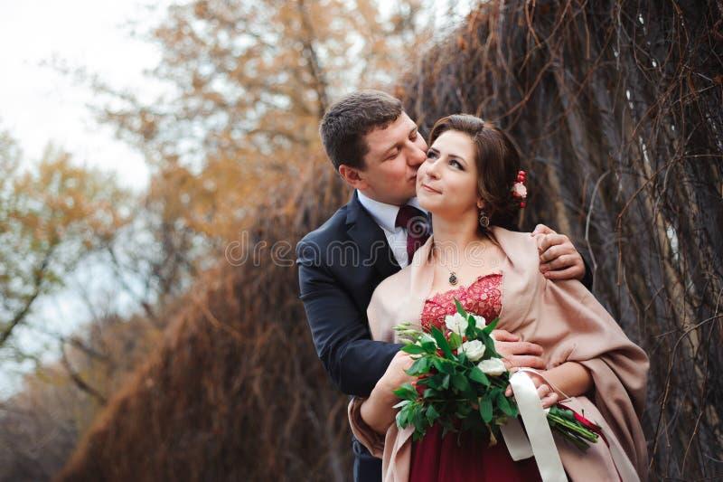 Portret van gelukkige jonggehuwden in de herfstaard Gelukkige en bruid en bruidegom die omhelzen kussen royalty-vrije stock afbeeldingen