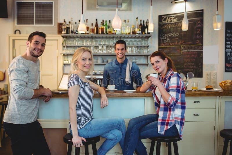 Portret van gelukkige klanten en kelner bij koffiehuis stock foto's