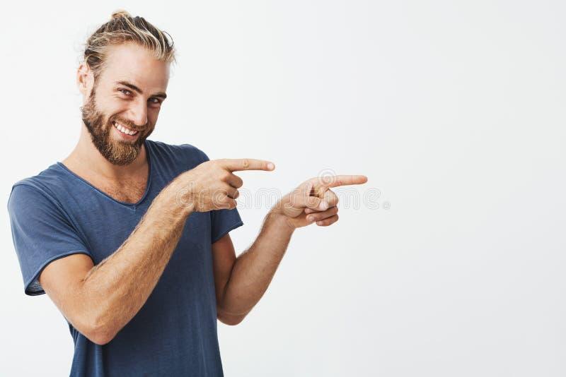 Portret van gelukkige knappe kerel met baard die vreugdevol en opzij met wijsvingers op beide handen glimlachen richten exemplaar royalty-vrije stock afbeeldingen