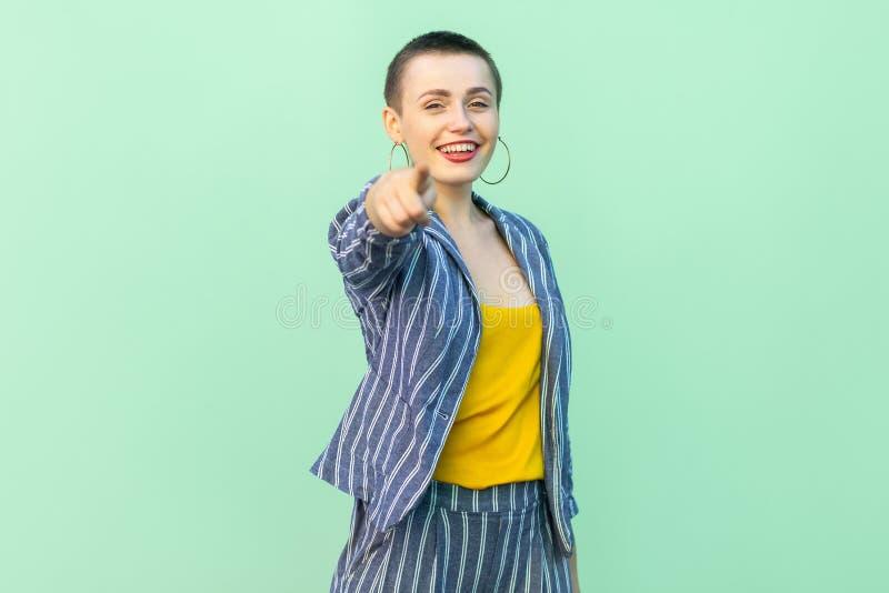 Portret van gelukkige knappe mooie korte haar jonge vrouw in toevallige gestreepte kostuum status bekijkend en richtend op camera stock foto