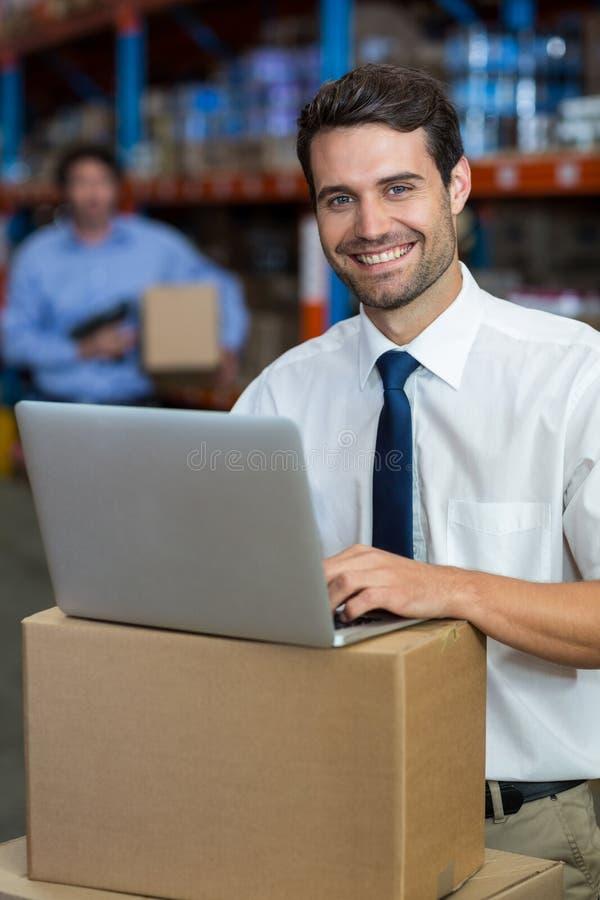 Portret van gelukkige manager die laptop met behulp van gezet op karton royalty-vrije stock fotografie