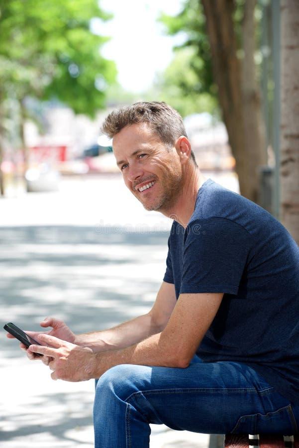Portret van gelukkige mensenzitting op parkbank met cellphone royalty-vrije stock fotografie