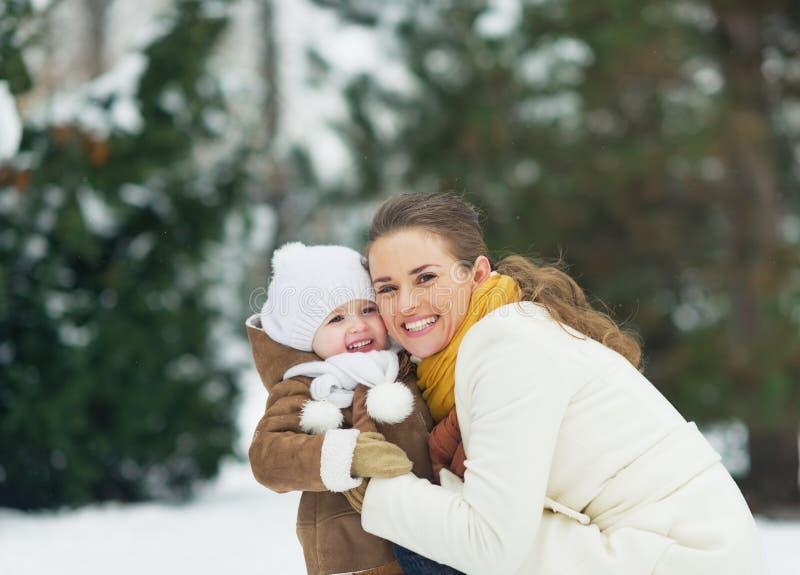 Portret van gelukkige moeder en baby in de winterpark stock afbeeldingen
