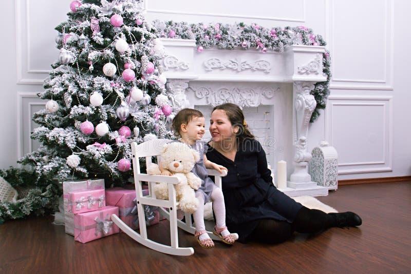 Portret van gelukkige moeder en de aanbiddelijke snuisterij van de babyholding tegen binnenlandse feestelijke achtergrond met Ker royalty-vrije stock fotografie