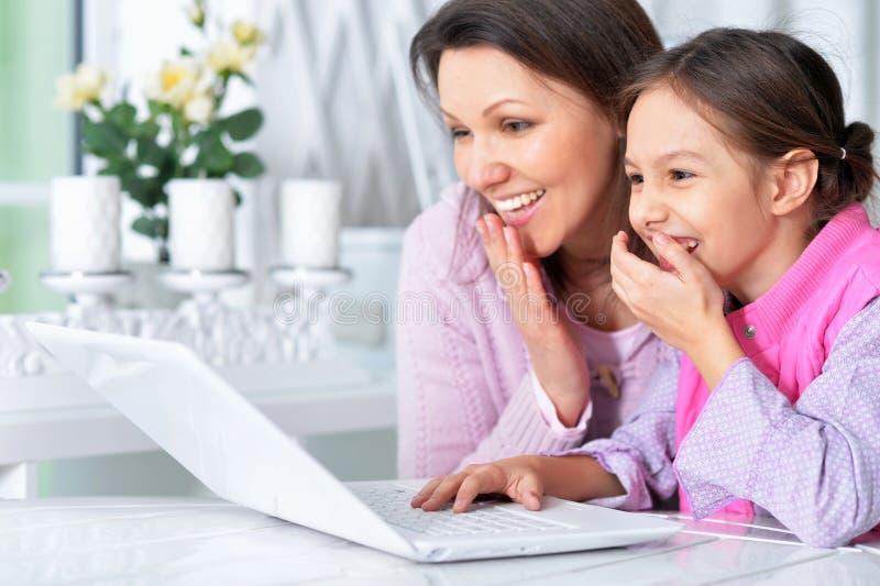 Portret van gelukkige moeder en dochter die laptop samen met behulp van stock afbeeldingen